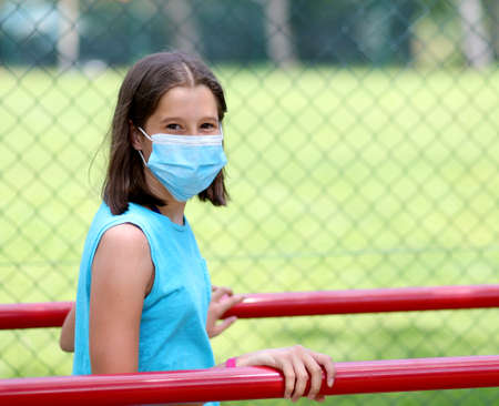 young girl does parallel gymnastics with surgical mask to protect herself from coronavirus Stock Photo