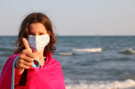 pretty girl with surgical mask at the sea with a bathrobe does the thumbs up to confirm that everything is fine