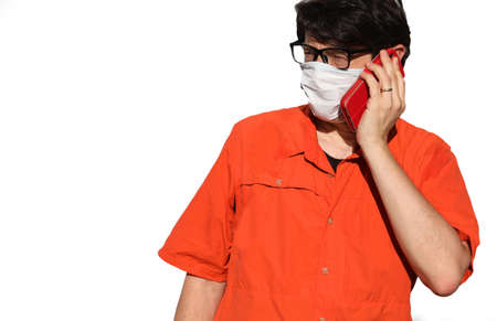 bespectacled person with mask and orange shirt while telephoning on white background Stock Photo
