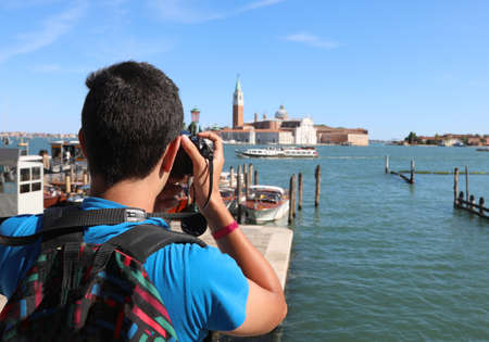young photographer with backpack on his shoulders while taking a photograph at the bell tower of Sait George Church in Venice in Italy