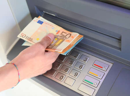 hand withdrawing money from the ATM with European banknotes in Europe Фото со стока
