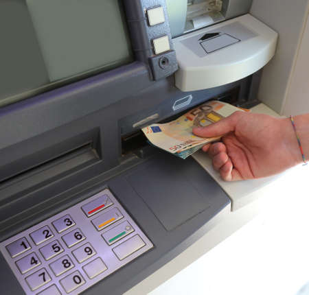 ATM with the keyboard and the hand that picks up the banknotes European Currency