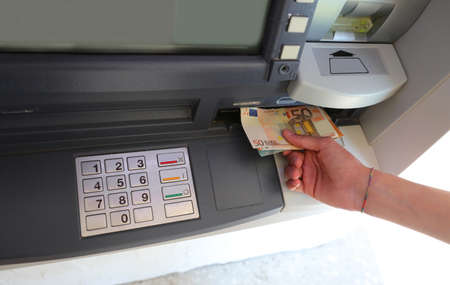 ATM cash machine with keyboard and hand picking up European currency banknotes