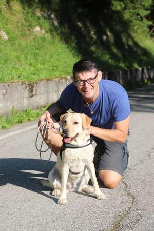man with glasses posing along the street with his purebred dog Labrador Retriever