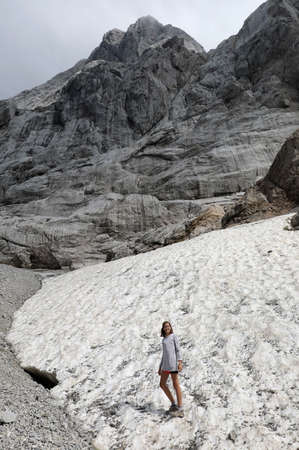 little girl above the ice of a perennial glacier in the mountains during a summer hike