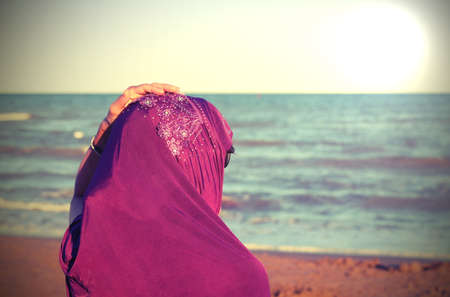 young girl with hand on veil on head by the sea in summer with special toned effect and the sun