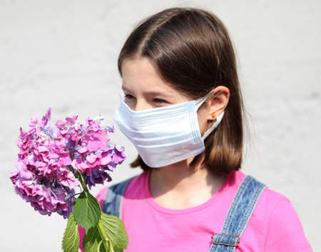 beautiful girl with brown hair and surgical mask with a hydrangea flower Stock Photo