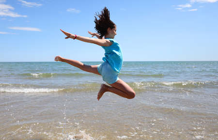 athletic girl takes an amazing jump over the sea on the shore of the beach in summer