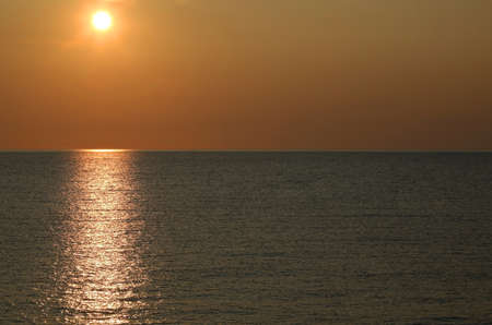 breathtaking sunset over the sea with warm orange red tones and sun reflection on the water Stock fotó