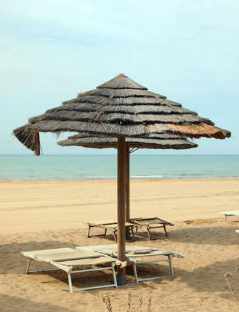 large bamboo sun umbrella on the seashore without people and empty deck chairs