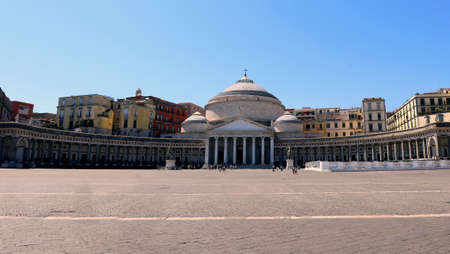 main Square of Naples City in Italy called piazza Plebiscito that means plebiscite Square with the large church surmounted by a big dome with few people due to the lockdown