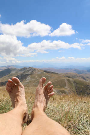 barefoot feet of the walker after hiking in the high mountains while resting