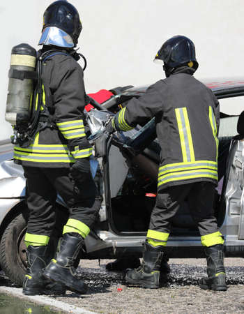 Firefighters with apparatus breathing during the rescue after the crash and the broken car