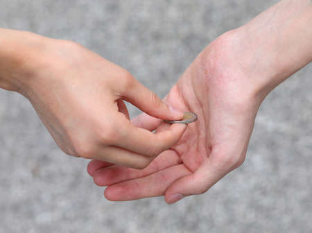 two hands of children a coin while giving alms