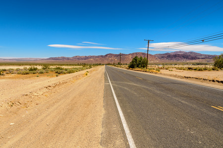 View of a desert road in Calico direction Stock Photo