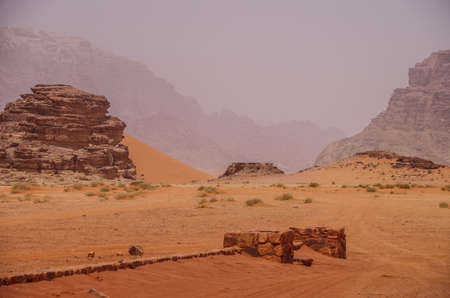 Landscape with ancient stone wall on a foggy day in Wadi Rum, Jordan
