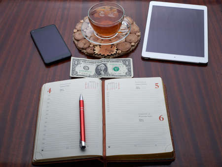 On the wooden table is a plate, a cup of tea, a cell phone, Address Book, Pen, Dolar, money Stock Photo