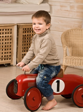 toy cars: A little boy riding on the red toy car