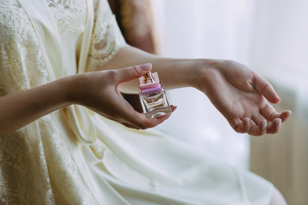 The girl sprinkles herself with perfume