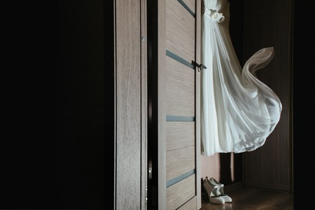hanging on the wardrobe wedding dress is developing under the gust of wind, at the bottom are white shoes of the bride Foto de archivo