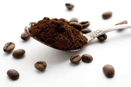 Ground coffee and coffee beans, white background
