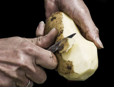 Mans hands peeling potato with serrated knife fading into black background. Shot with macro lens, very detailed image