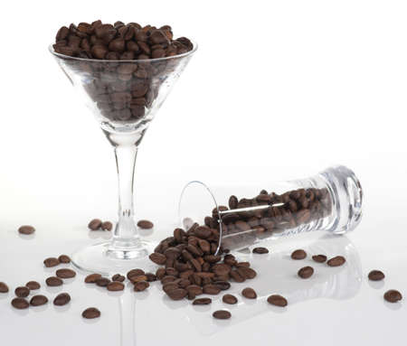 overfilled: Two bar glasses with coffee beans