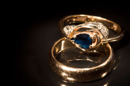 Two golden rings with sapphire and diamonds isolated on black with reflection, light painting, full frame camera shot photo
