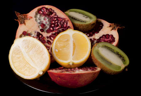 Plate of  fresh cut fruits isolated on black photo