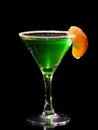 absent: Back lit martini glass with absinthe cocktail decorated by salt rim and tangerine slice, focus is on the salt crust, unsharpened Stock Photo