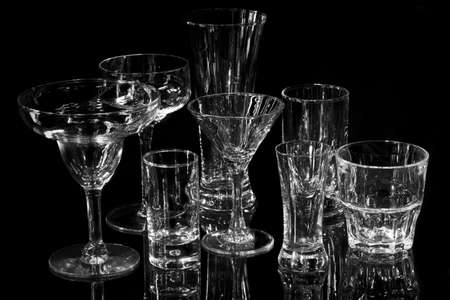Collection of various bar glasses isolated on black with reflection, monochrome photo