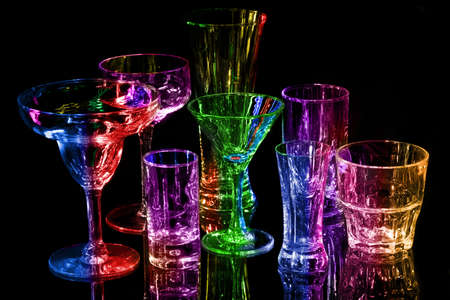 Collection of various bar glasses isolated on black with reflection, multi-colored photo