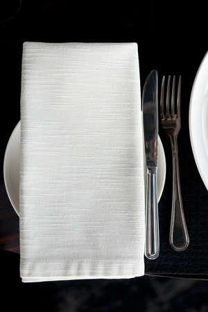 white napkin: Napkin and silverware on restaurant table