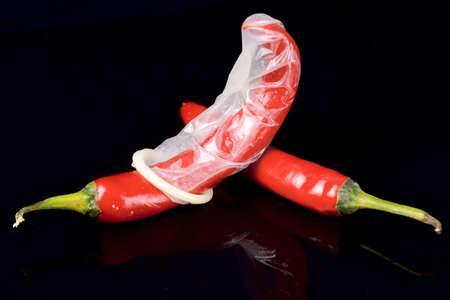 chiles picantes: Pasi�n bajo control - pimientos picantes y el cond�n de l�tex Foto de archivo