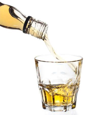 botella de whisky: Whisky a raudales en vidrio, aislado, recorte incluido