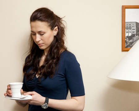 Thoughtful woman with cup of coffee  against a beige wall photo