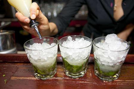 highball: Female bartender pouring juice in glass, retro styled bar