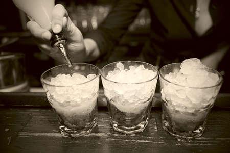 bartender: Female bartender pouring juice in glass, retro styled bar