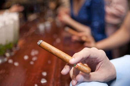 Man smoking cigar at bar counter, shallow focus photo