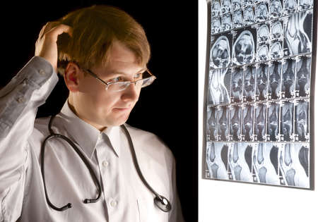 Puzzled radiologist looking at MRI in dark room photo