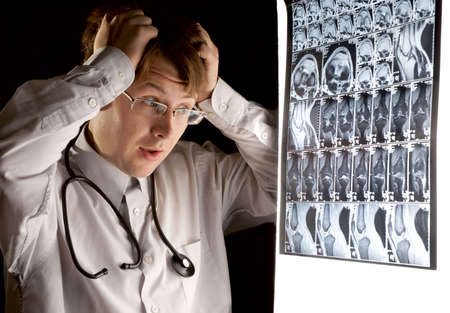 Young, doctor looking at the MRI scan with panic photo