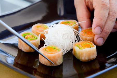 Chef arranging sushi dish with sticks, close-up photo