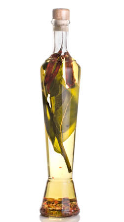Spicy olive oil with peppercorn, small chili peppers and bay leaves isolated on white photo