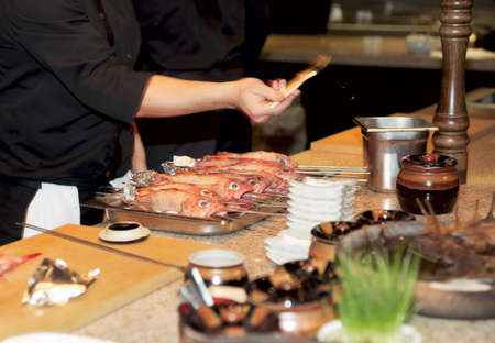 Chef prepares fish for grill - adds oil and seasoning with brush, motion blur on hand photo