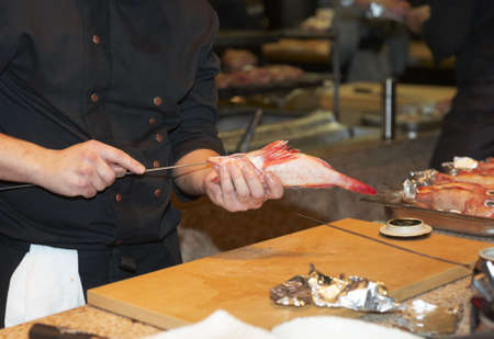 Chef prepares fish for grilling on open fire  photo