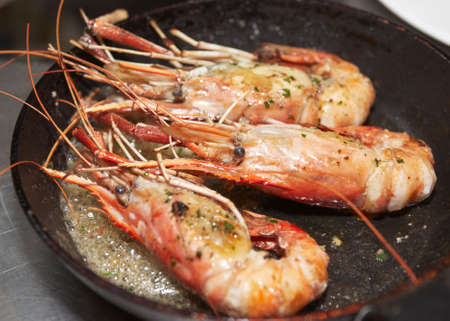 Giant prawns on hot pan stir fried in butter photo