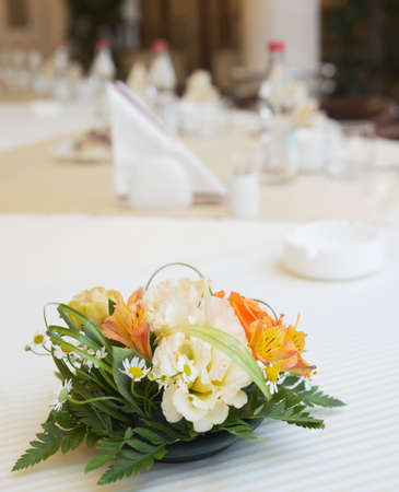 Table arrangement with flowers in large conference hall photo