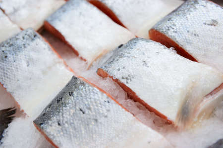 Salmon pieces on cooled market display, closeup photo