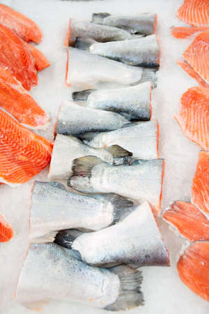 Salmon tails and fillet on cooled market display in supermarket photo