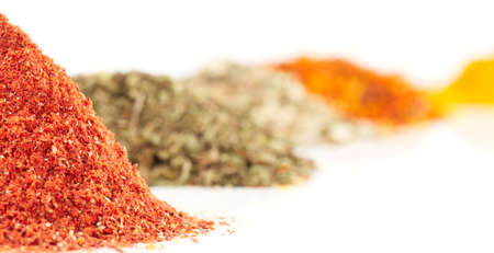 Piles of different spices, focus is on the first (paprika) photo